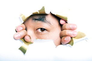 Young Korean man looking through ripped paper holeの写真素材 [FYI03649428]
