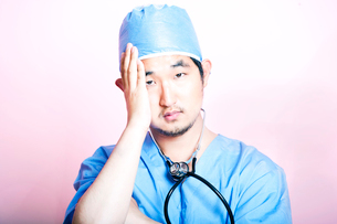Young tired Asian surgeon wearing scrubs and looking stressedの写真素材 [FYI03649431]
