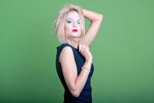 Sexy blonde businesswoman on green backgroundの写真素材 [FYI03649441]