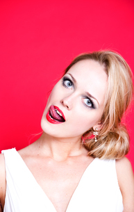 Caucasian woman wearing white dress on red background licking her lipsの写真素材 [FYI03649447]