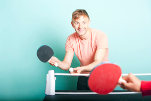 Caucasian man playing table tennis with friendの写真素材 [FYI03649451]