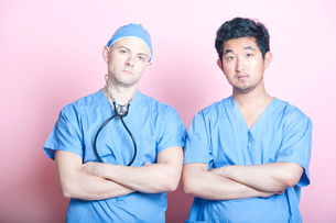 Portrait of two male surgeons standing with arms crossed over pink backgroundの写真素材 [FYI03649462]