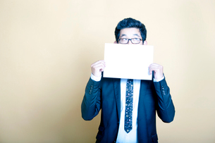 Asian businessman holding white blank signの写真素材 [FYI03649467]