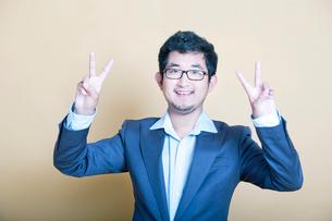 Stylish Asian man making 'peace' symbolsの写真素材 [FYI03649474]