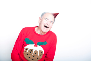 Senior adult man wearing a Christmas jumper and a red party hatの写真素材 [FYI03649482]