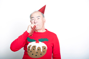 Senior adult man wearing Christmas jumper blowing party blowerの写真素材 [FYI03649484]