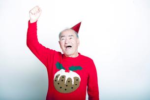 Senior adult man wearing Christmas jumper raising his arm in the airの写真素材 [FYI03649485]