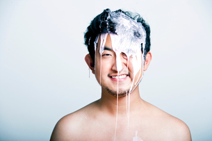 Shirtless young man with pink paint falling on his head against gray backgroundの写真素材 [FYI03649489]
