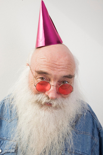 Portrait of senior man wearing red glasses and party hat over gray backgroundの写真素材 [FYI03649553]