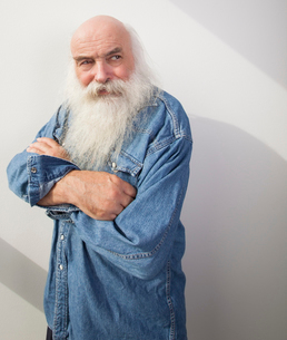 Senior man with arms crossed looking away over gray backgroundの写真素材 [FYI03649555]