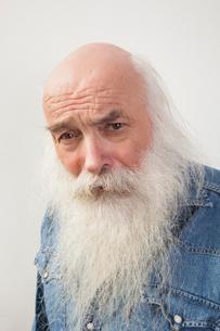 Portrait of suspicious senior man over gray backgroundの写真素材 [FYI03649556]