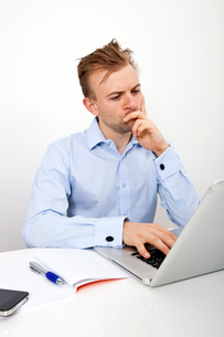 Thoughtful businessman using laptop at desk in officeの写真素材 [FYI03649585]