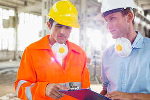 Male architects in protective workwear discussing at construction siteの写真素材 [FYI03649595]