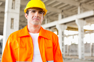 Handsome mid adult man wearing protective workwear at construction siteの写真素材 [FYI03649607]