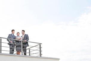 Businesspeople standing at terrace railings against skyの写真素材 [FYI03649623]