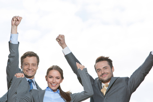 Portrait of excited businesspeople with arms raised on terrace against skyの写真素材 [FYI03649628]