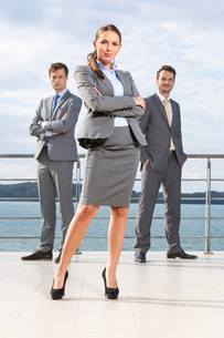 Full length portrait of confident businesswoman standing with coworkers on terrace against skyの写真素材 [FYI03649633]