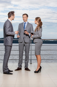 Full length of young businesspeople holding wineglasses while communicating on terraceの写真素材 [FYI03649644]