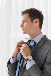 Thoughtful businessman loosening necktie in hotelの写真素材 [FYI03649661]