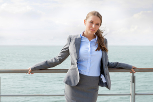 Portrait of confident businesswoman leaning on terrace railingsの写真素材 [FYI03649685]