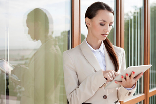 Young businesswoman using digital tablet against office buildingの写真素材 [FYI03649702]
