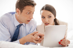 Shocked business couple using digital tablet in hotelの写真素材 [FYI03649717]