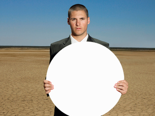 Portrait of young businessman holding blank signの写真素材 [FYI03649764]
