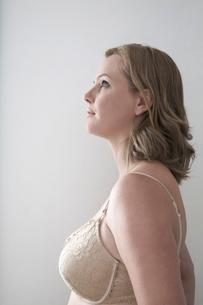 Woman in bra looking away over gray backgroundの写真素材 [FYI03649769]