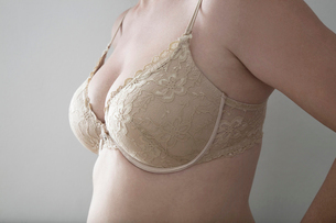 Midsection of woman in bra over gray backgroundの写真素材 [FYI03649773]