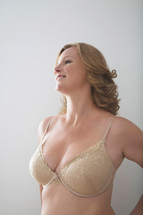 Woman in bra standing against gray backgroundの写真素材 [FYI03649776]