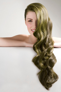 Beautiful woman with long green dyed hair against gray backgroundの写真素材 [FYI03649788]