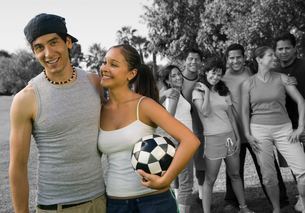 Happy couple holding soccer ball enjoying with friends at parkの写真素材 [FYI03649792]