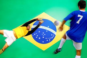 Soccer player scoring goal in front of Brazilian Flagの写真素材 [FYI03649796]