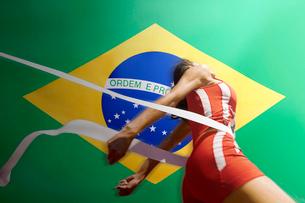 Runner Breaking through the finishing line tape over Brazilian flagの写真素材 [FYI03649797]