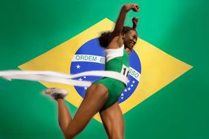 Runner Breaking through the finishing line tape over Brazilian flagの写真素材 [FYI03649798]