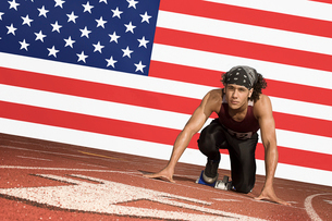 Runner on a track in starting block in front of US flagの写真素材 [FYI03649802]