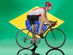 Male Cyclist cycling in front of Brazilian Flagの写真素材 [FYI03649823]