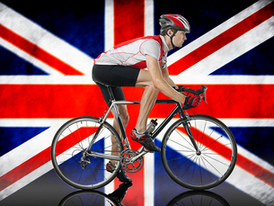 Male Cyclist cycling in front of Union Jack Flagの写真素材 [FYI03649824]