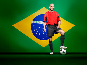 Soccer player standing in front of Brazilian flagの写真素材 [FYI03649828]