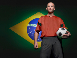 Soccer player standing in front of Brazilian flagの写真素材 [FYI03649831]