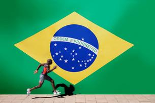 Athlete running past Brazilian flagの写真素材 [FYI03649837]