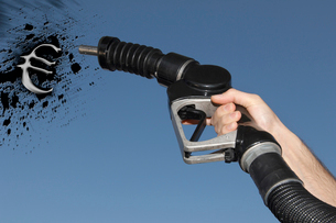 Hand holding Fuel hose spraying petrol oil in the shape of the Euro Symbolの写真素材 [FYI03649838]