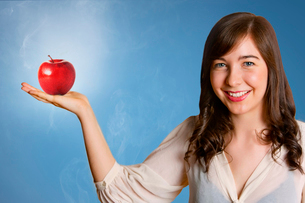 Beautiful young woman holding red appleの写真素材 [FYI03649852]