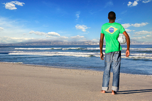 Rear view of man standing wearing Brazilian t shirt with football on a beachの写真素材 [FYI03649855]
