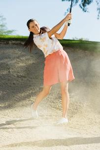 Female golfer hitting ball from sand trapの写真素材 [FYI03649915]