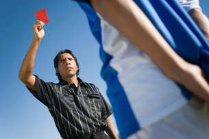 Referee holding up red card portrait low angle viewの写真素材 [FYI03649917]