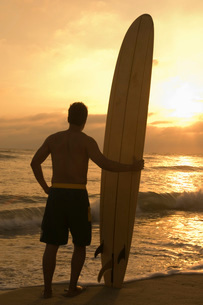 Surfer standing on beach holding surfboard watching sunset back viewの写真素材 [FYI03649928]