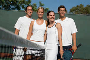 Mixed Doubles Tennis Players standing at Net arms aroundの写真素材 [FYI03649953]