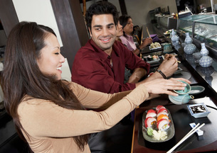Young people eating sushi with chopsticks in restaurantの写真素材 [FYI03649979]