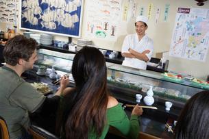 People eating at sushi barの写真素材 [FYI03649981]